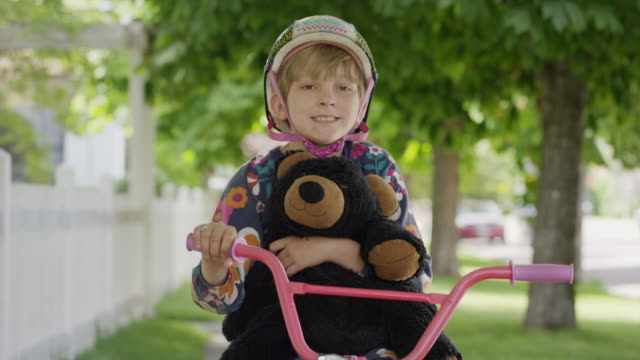 vídeos de stock e filmes b-roll de portrait of boy in pajamas sitting on bicycle holding teddy bear / provo, utah, united states - provo