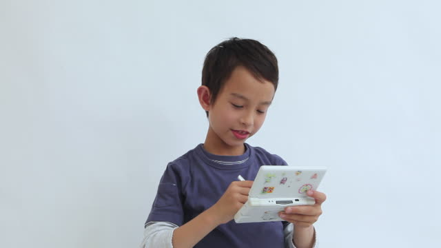 ms portrait of boy (8-9) playing on handheld video game / shibuya, tokyo, japan - handheld video game stock videos & royalty-free footage