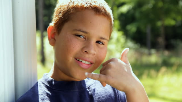 cu portrait of boy (10 -11) showing 'call me' gesture / madison, florida, usa - freckle stock videos & royalty-free footage
