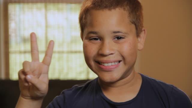 cu portrait of boy (10 -11) showing peace sign and smiling / madison, florida, usa - 10 11 år bildbanksvideor och videomaterial från bakom kulisserna