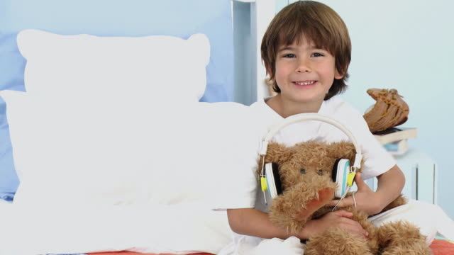 ms portrait of boy (4-5) sitting on bed with teddy bear wearing headphones / cape town, south africa - teddy boy stock videos & royalty-free footage