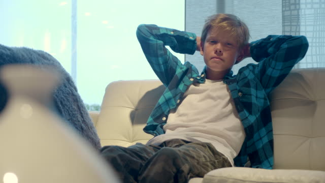 portrait of boy sitting on the sofa and looking to the camera in the interior. rainy window on the background. - un ragazzo adolescente video stock e b–roll