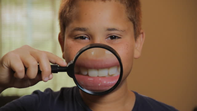 cu portrait of boy (10 -11) smiling through magnifying glass / madison, florida, usa - 歯点の映像素材/bロール