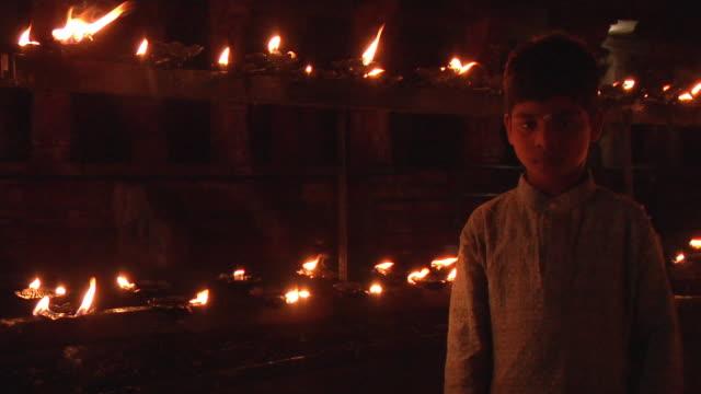 MS, Portrait of boy (8-9) standing in front of lit oil lamps, Hampi, Karnataka, India