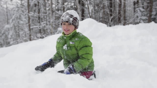 MS Portrait of boy (8-9) throwing snow at camera / Franconia, New Hampshire, USA