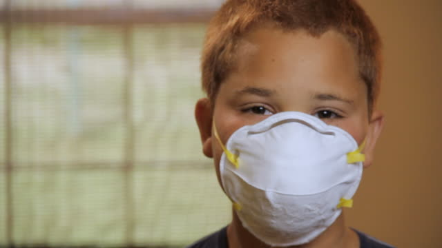 cu portrait of boy (10 -11) wearing protection mask / madison, florida, usa - surgical mask stock videos & royalty-free footage