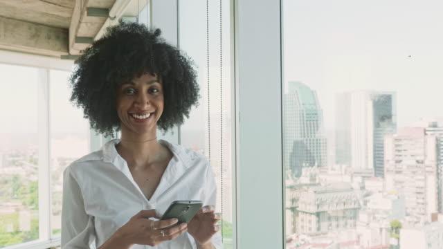 携帯電話を見ているブラジルのビジネスウーマンの肖像 - white collar worker点の映像素材/bロール