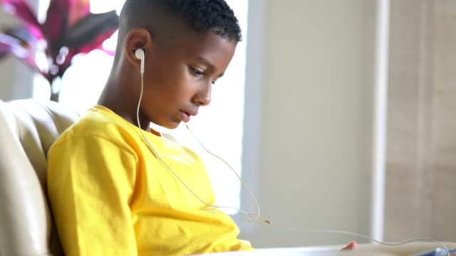 portrait of brazilian kid listening music on the tablet - headphones stock videos & royalty-free footage