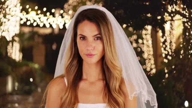vídeos de stock e filmes b-roll de portrait of bride in wedding dress and veil standing outside, looking at camera - vestido branco