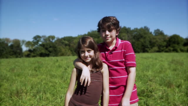 SLO MO MS Portrait of brother (12-13) and sister (8-9) in meadow / Hampton, New Jersey, USA