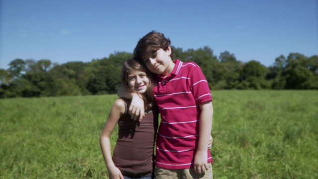 slo mo ms portrait of brother (12-13) and sister (8-9) in meadow / hampton, new jersey, usa - sister stock videos and b-roll footage