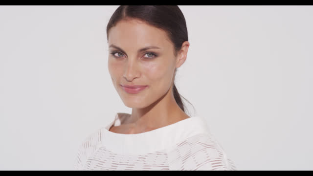 vidéos et rushes de portrait of brunette woman in white dress turning 180 degrees to camera smiling - trentenaire