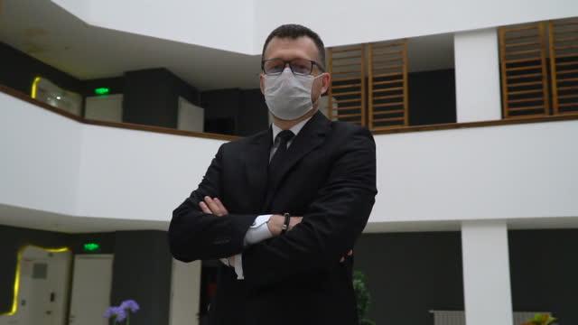 vídeos y material grabado en eventos de stock de retrato del dueño del hombre de negocios con máscara facial en el vestíbulo de la oficina moderna - brazos cruzados
