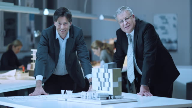 DS Portrait of business men standing by architectural model
