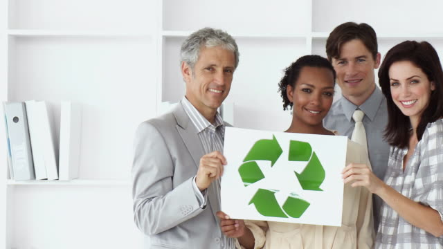 MS PAN Portrait of business team holding recycling sign / Cape Town, Western Cape, South Africa