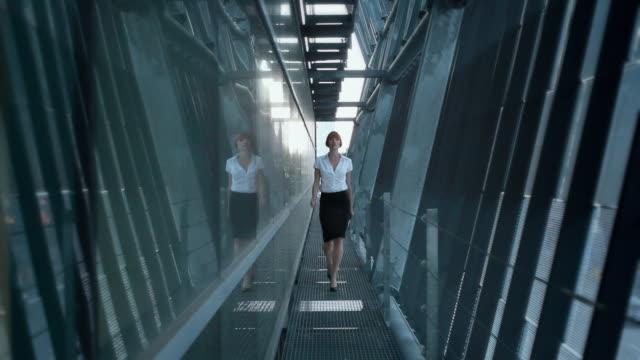 ws ms portrait of business woman approaching camera in walkway, los angeles, california, usa - 30代点の映像素材/bロール