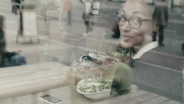 Portrait of business woman smiling at camera, eating a salad for lunch in restaurant in Berlin