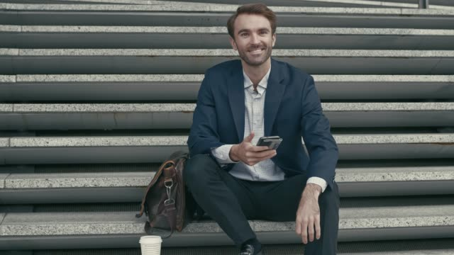 Porträt des Kaufmanns prüfen sein Handy auf der Straße