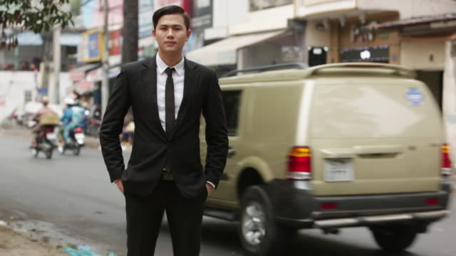 WS Portrait of businessman in suit, looking at camera in front of busy street of motor scooters