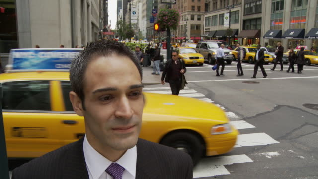 T/L CU Portrait of businessman on busy street / New York City, New York, USA