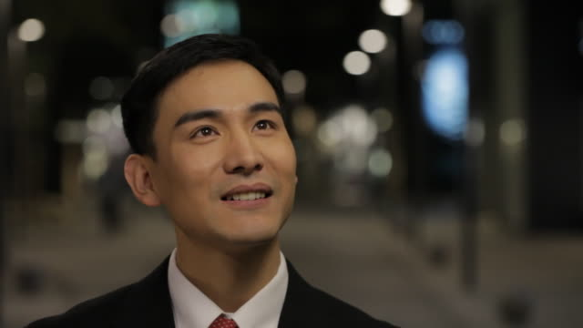 CU Portrait of businessman smiling, standing on street at night / China