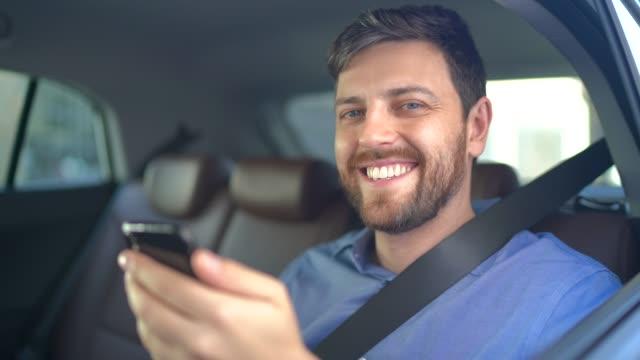 vídeos de stock e filmes b-roll de portrait of businessman using digital tablet at passenger seat inside a car - dividir