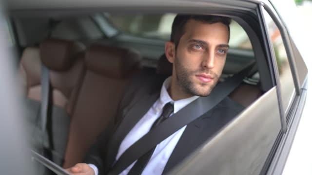 vídeos de stock, filmes e b-roll de retrato do homem de negócios que usa a tabuleta digital dentro do carro - viagem de negócios