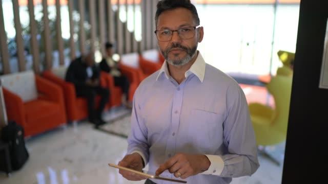 vídeos de stock, filmes e b-roll de retrato do homem de negócios que usa a tabuleta digital - cabelo grisalho