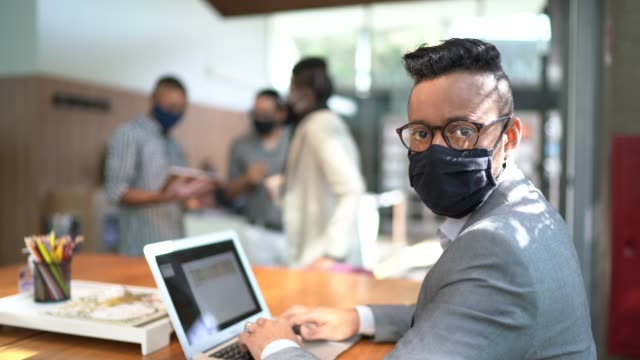 portrait of businessman using laptop at office's lobby - with face mask - employee stock videos & royalty-free footage