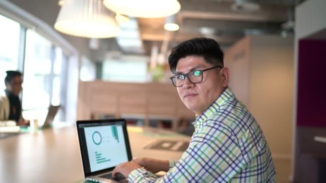 stockvideo's en b-roll-footage met portret van zakenman die laptop op het werk gebruikt - peruaanse etniciteit