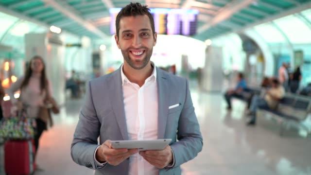 vídeos de stock, filmes e b-roll de retrato do homem de negócios que usa a tabuleta no aeroporto - viagem de negócios