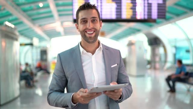 vídeos de stock, filmes e b-roll de retrato do homem de negócios que usa a tabuleta no aeroporto - área de embarque de aeroporto
