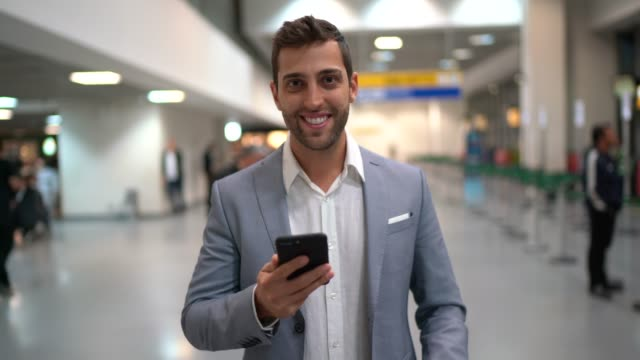 Portrait of businessman waiting and using mobile on airport
