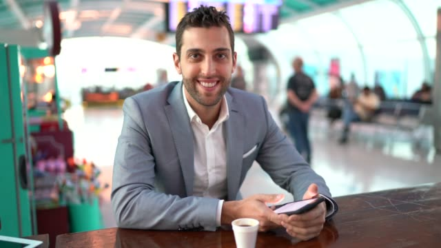 Portrait of businessman working and using mobile at coffee time on airport