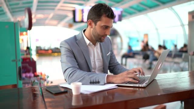 vídeos de stock, filmes e b-roll de retrato do homem de negócios que trabalha e que usa móvel no tempo do café no aeroporto - oriente médio etnia