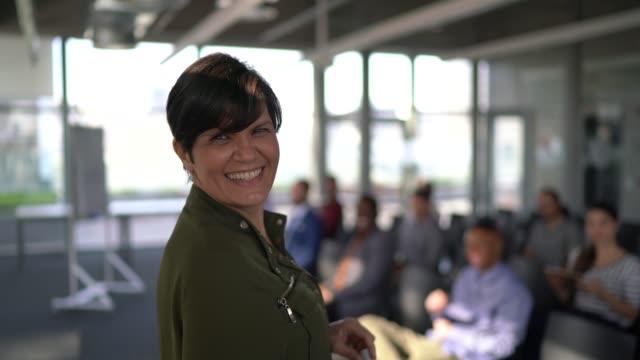 vidéos et rushes de verticale de femme d'affaires prononçant un discours pendant une conférence - directrice