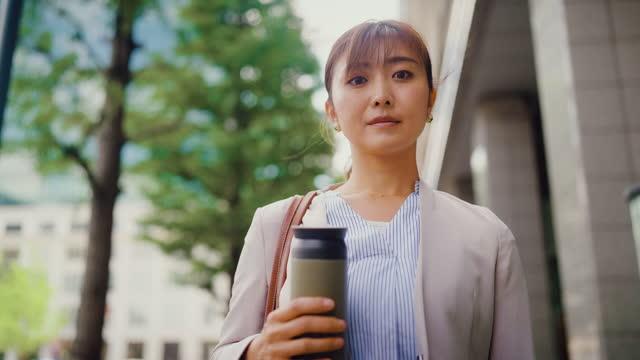 再利用可能な水筒を持ち、街のカメラのために微笑むビジネスウーマンの肖像画 - standing点の映像素材/bロール