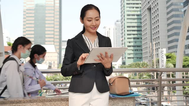 portrait of businesswoman in a tablet computer with a business center behind, outdoor. business woman on a meeting and waiting business partner and holding a tablet in hands. - 2015 stock videos & royalty-free footage