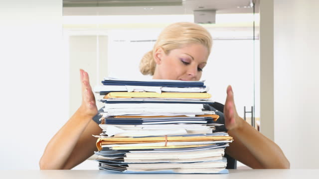 Portrait of businesswoman overwhelmed with large pile of work
