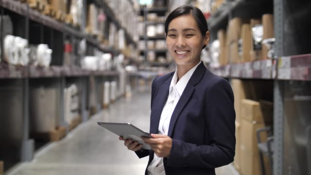portrait of businesswoman owner using digital tablet in warehouse and turning towards camera, confidence - employee video stock e b–roll