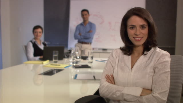ms portrait of businesswoman sitting with arms crossed at conference table in board room, colleagues in background, smiling / new york city, new york, usa - male with group of females stock videos & royalty-free footage