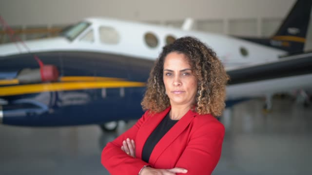 portrait of businesswoman standing in front of a corporate jet with arms crossed - one mature woman only stock videos & royalty-free footage