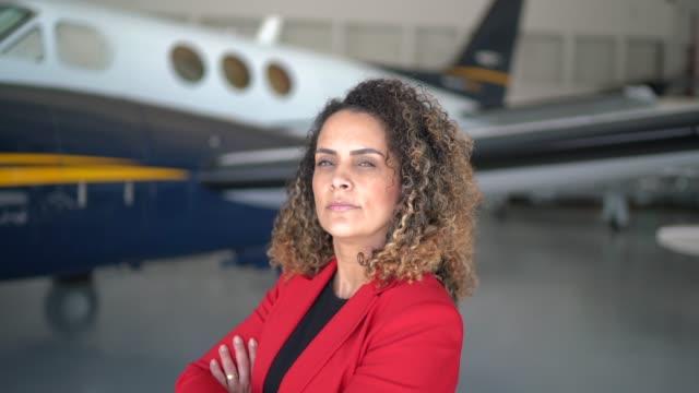 vídeos de stock, filmes e b-roll de retrato da mulher de negócios que está na frente de um jato corporativo com os braços cruzados - autoridade