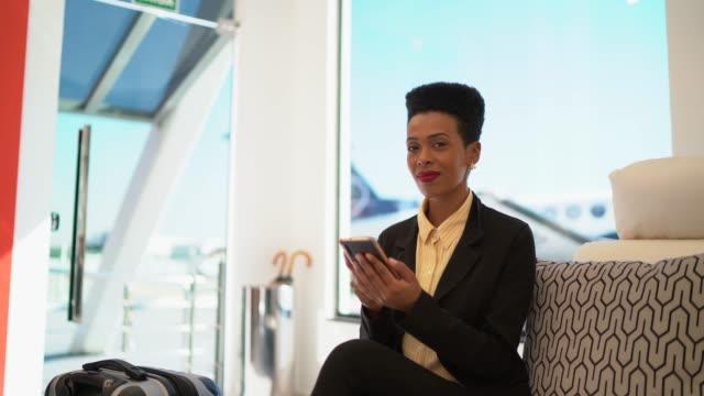 vídeos de stock, filmes e b-roll de retrato da mulher de negócios que usa o telemóvel dentro de uma sala vip do aeroporto - área de embarque de aeroporto