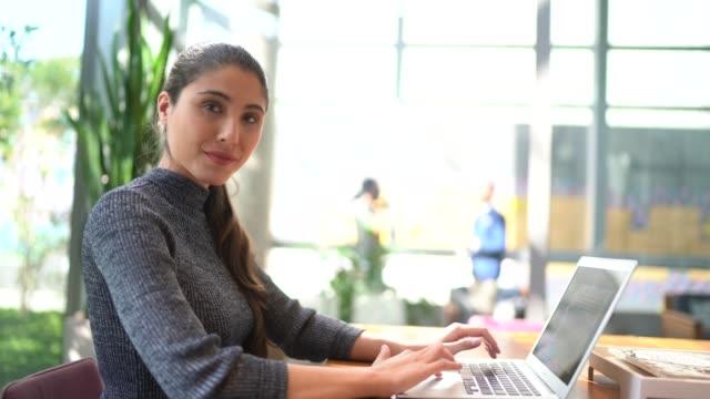 vídeos de stock e filmes b-roll de portrait of businesswoman using laptop at work - povo brasileiro