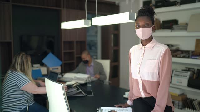 vídeos de stock, filmes e b-roll de retrato de empresária usando máscara facial em um escritório, colegas de trabalho ao fundo - gerente