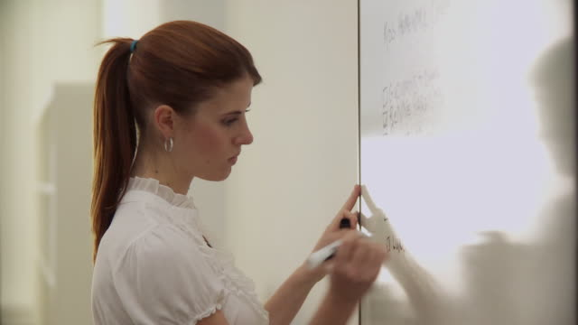 ms portrait of businesswoman writing on whiteboard / new york city, new york, usa - speech video stock e b–roll