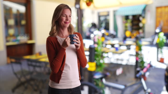 portrait of calm relaxed woman drinking coffee outside - tee warmes getränk stock-videos und b-roll-filmmaterial