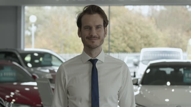 portrait of car sales man looking at camera in automotive dealership showroom - shirt and tie stock videos & royalty-free footage