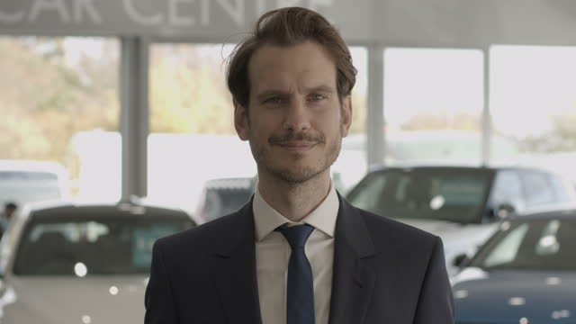portrait of car sales man looking at camera in automotive dealership showroom - one mid adult man only stock videos & royalty-free footage